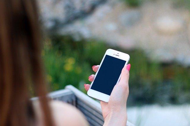 Žena držící mobilní telefon v ruce