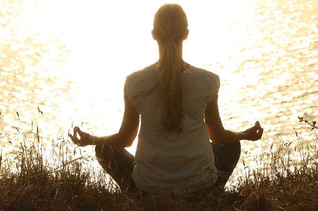 Žena meditující u vody